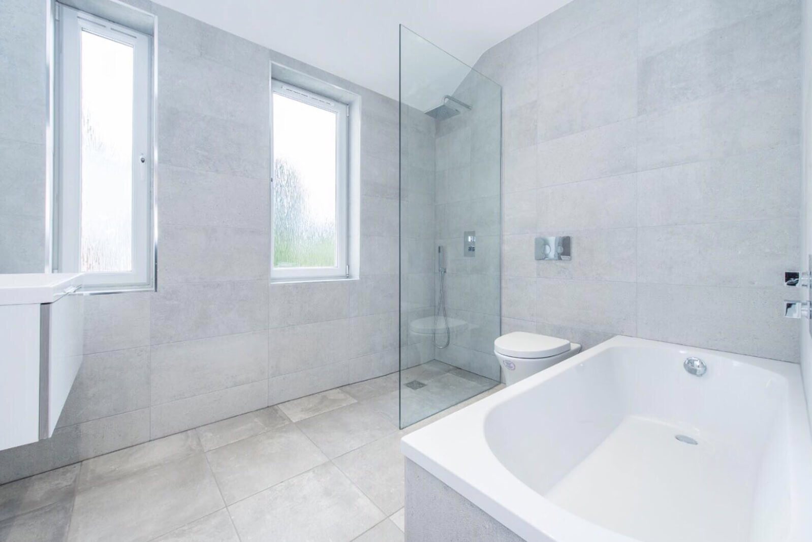 Modern wet room style bathroom with walk in shower. White bathroom units including large bath. Fully tiled walls with two single windows. Tiled floor.
