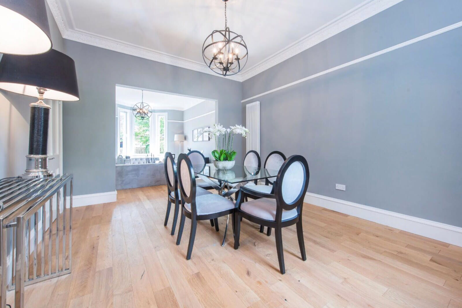 Large dining area with glass table and 6 dining chairs. Modern console table with two lamps. View of lounge area with wooden flooring throughout.