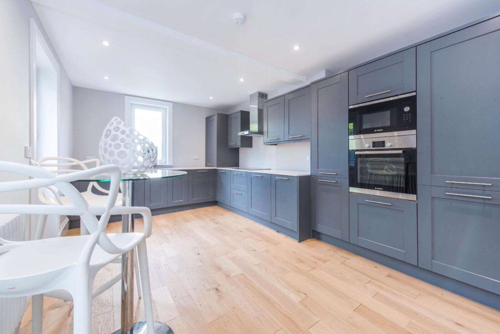 Large modern kitchen with grey panelled units and integrated appliances. Small tall table and two chairs. Wooden flooring throughout.