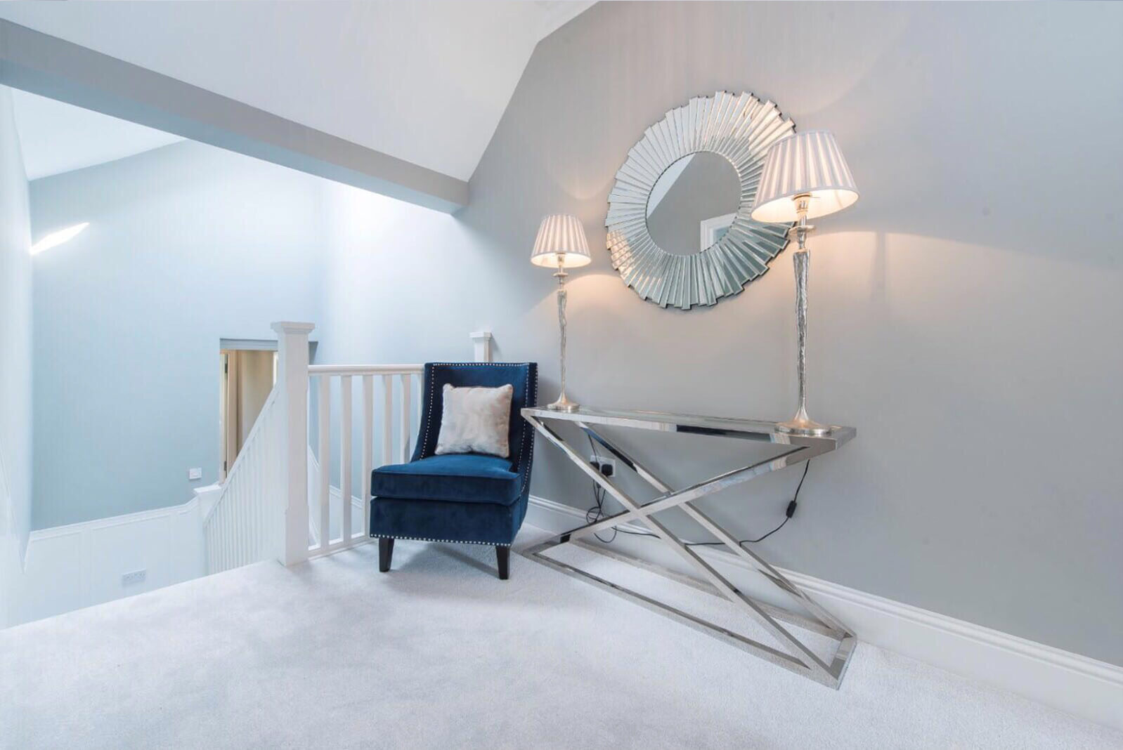 Large open area at top of stairs furnished with fabric chair and console table, mirror and lamps