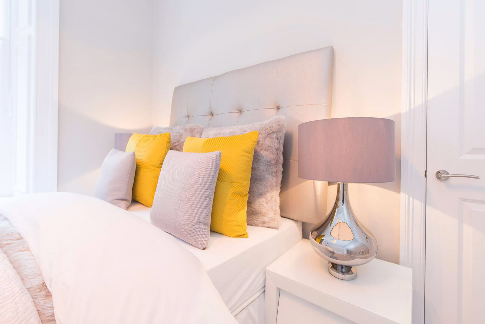 Dressed bed with six cushions of varying size. White bedside table with lamp.