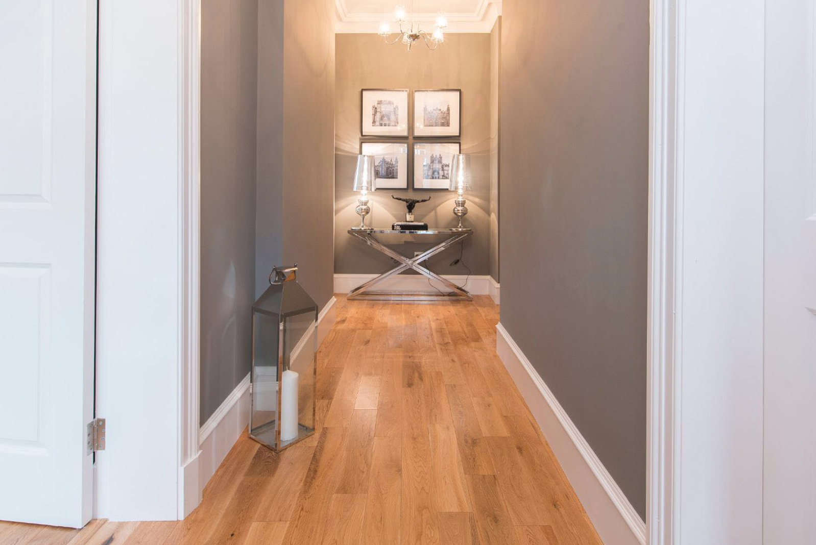 Hallway with wooden flooring and furnished with console table, lamps and four hanging pictures