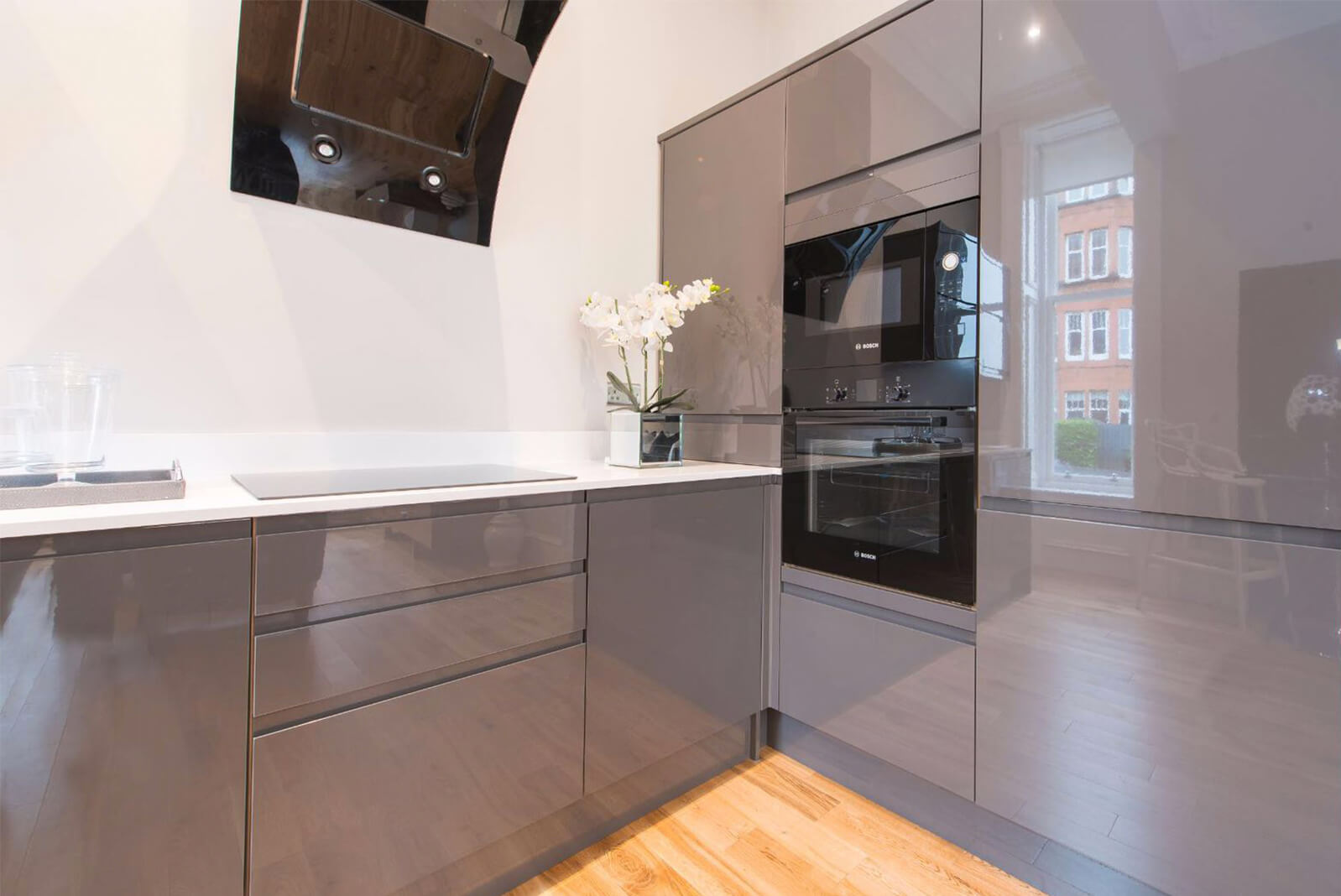 Grey kitchen units with integrated Bosch oven and microwave. Ceramic hob and modern extractor fan.