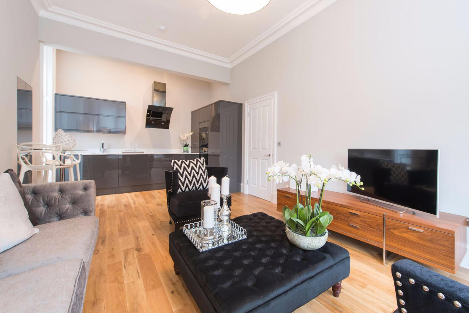 Furnished open plan lounge looking into kitchen area. Wooden flooring and cornicing on ceiling.
