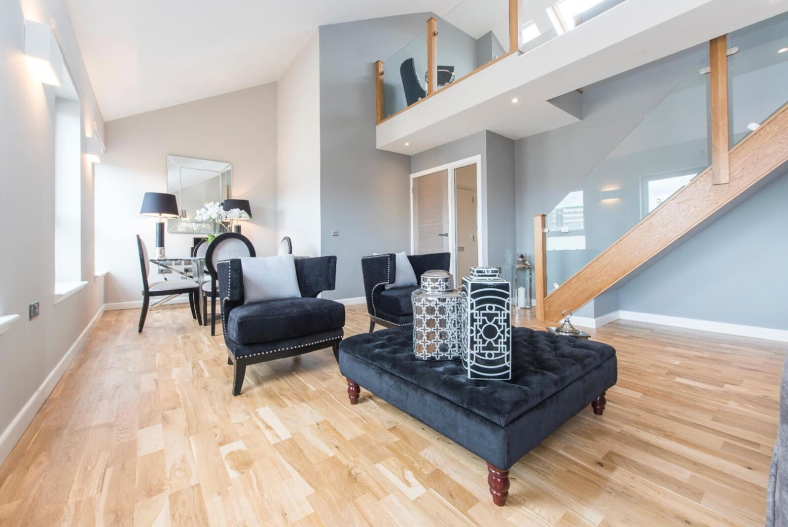 Furnished open plan lounge area with staircase to upper level. Dining area with square glass table and four dining chairs.