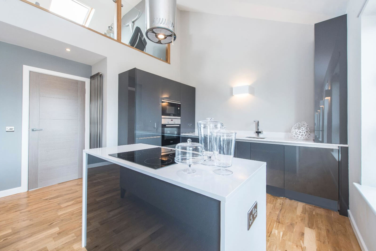 Modern open plan kitchen with grey, high gloss units and integrated appliances. Island unit with ceramic hob and modern, hanging extractor fan. Wooden flooring.