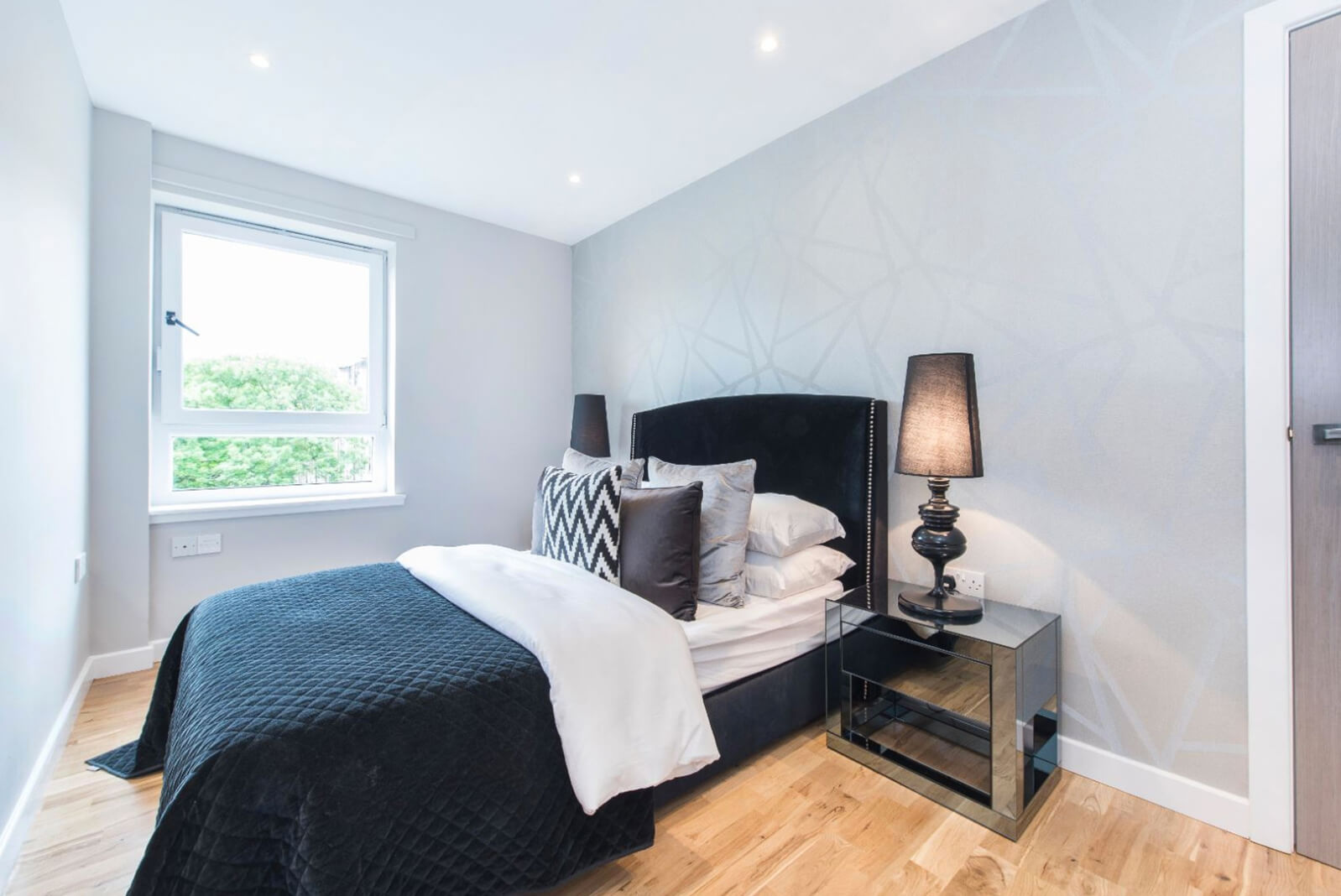 Dressed double bed with bedside tables either side. Modern geometric wallpaper on one wall and wooden flooring. Single window.