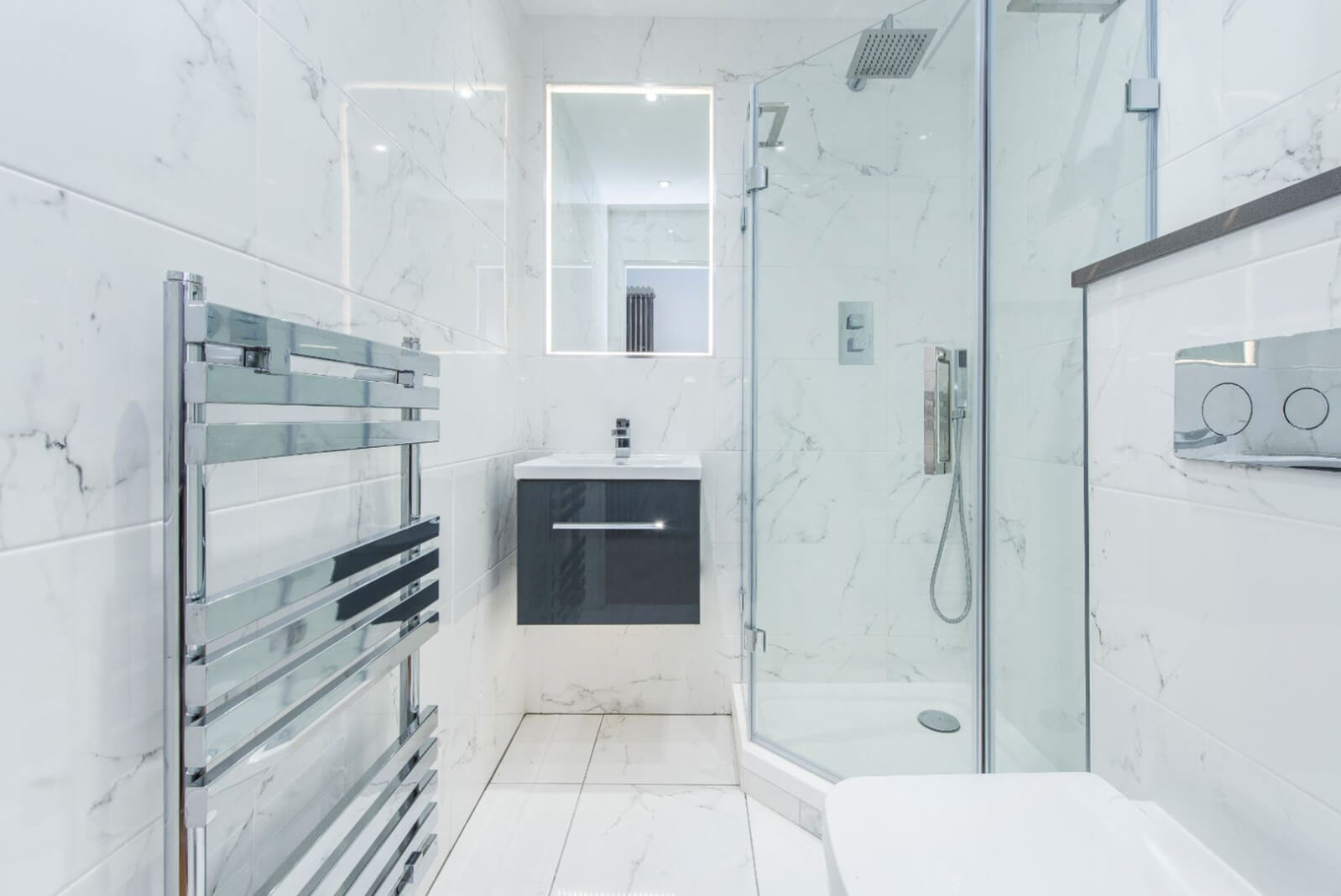 Modern, fully tiled bathroom with walk in shower and heated towel rail.