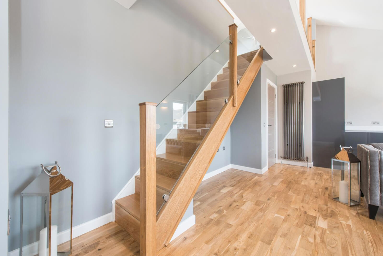 Modern, wooden staircase with glass panels leading up to mezzanine area.