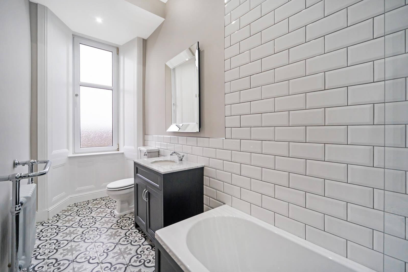 Bathroom with partially white tiled walls and decorative floor tiles. Marble top hand basin, with white toilet and bath.