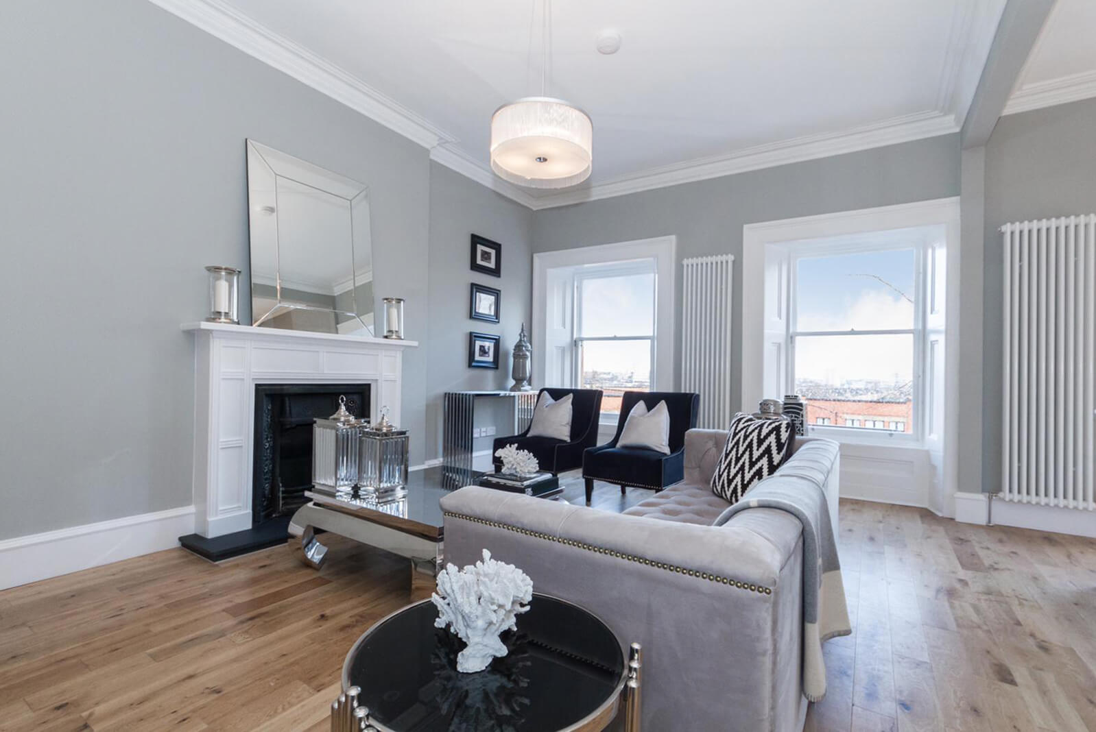 Large furnished lounge with wooden flooring, two windows and period style fireplace